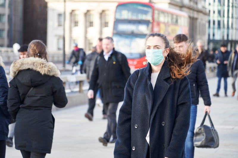 woman walking wearing a face mask
