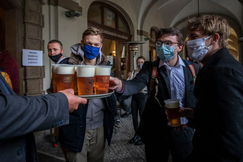 People drink beer at an outdoor seating section of a pub, as the Czech government lifted more restrictions allowing restaurants with outdoor areas to re-open