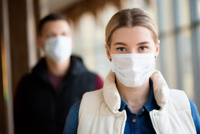 Man and woman wearing protective mask against transmissible infectious diseases