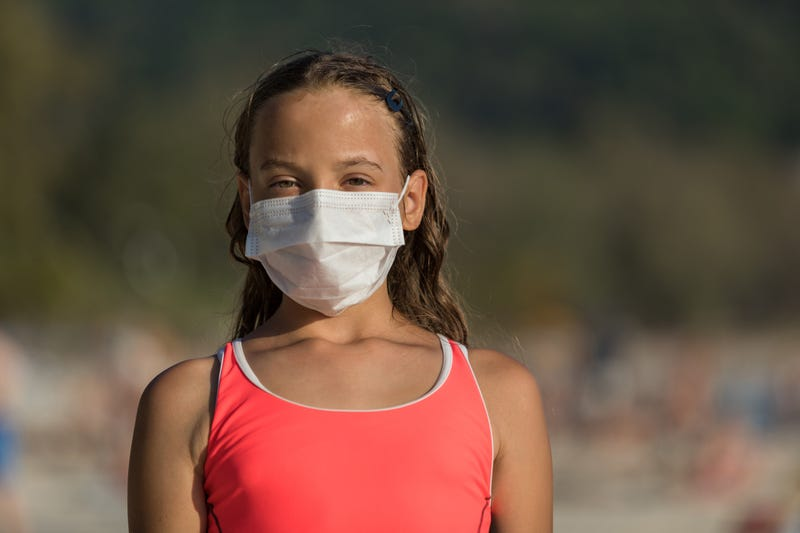 girl on beach wearing face mask