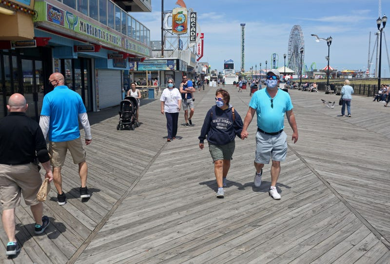 People traverse the Seaside Heights boardwalk as the state begins to reopen beaches and boardwalks amid the novel coronavirus pandemic on May 16, 2020 in Seaside Heights, New Jersey.