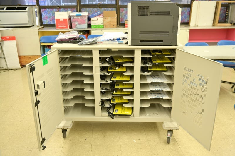 A cart is used to hold and organize school-owned laptops to be distributed to students in need for remote learning in Manhattan.