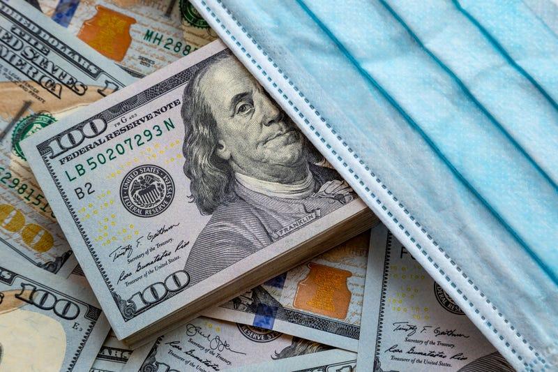 Dólares estadounidenses y una mascarilla médica