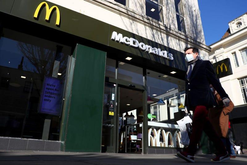 A man wearing a facemask walks past a McDonald's restaurant