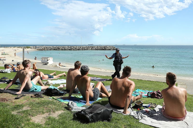 Police officers encourage beach goers to keep 1.5 metres social distance on March 26, 2020 in Perth, Australia.