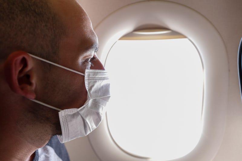 A man wearing a face mask on a flight.