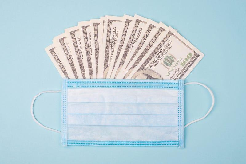 billetes de 100 dólares con una mascarilla médica