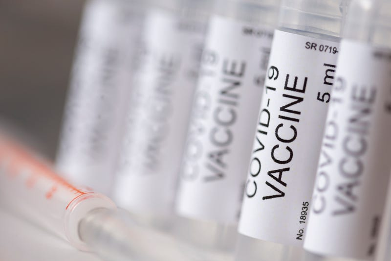 Detail of covid-19 vaccine vials and syringe; novel coronavirus treatment and prevention research concept