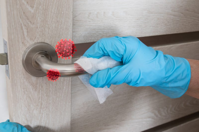 Wiping door knob with antibacterial disinfecting wipe for killing coronavirus.