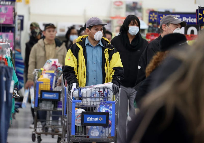 People wearing masks and gloves wait to checkout at Walmart on April 03, 2020 in Uniondale, New York