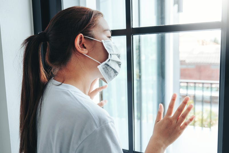 Asian woman in isolation at home for virus outbreak Coronavirus wearing a face mask quarantine herself