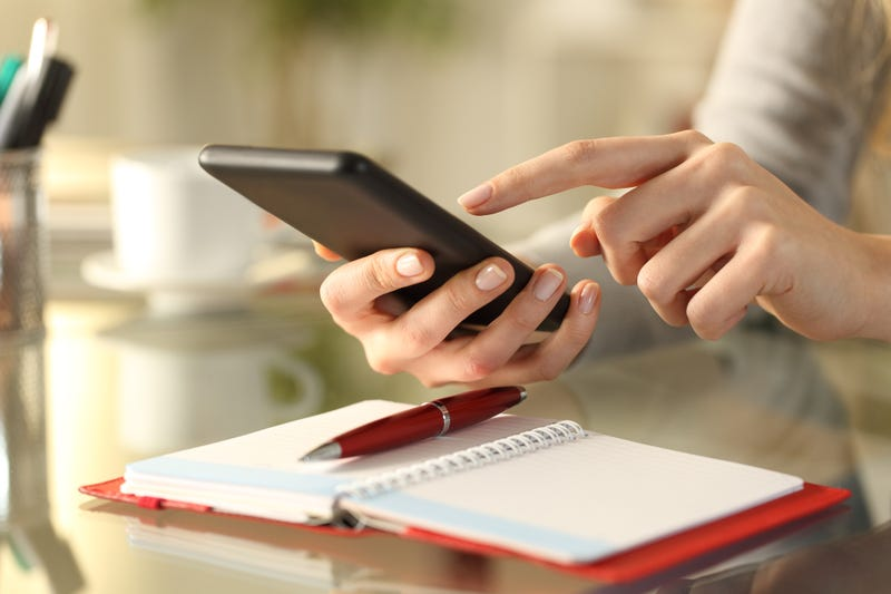 Close up of a woman's hands checking smart phone with personal organizer diary or agenda over the table at home.