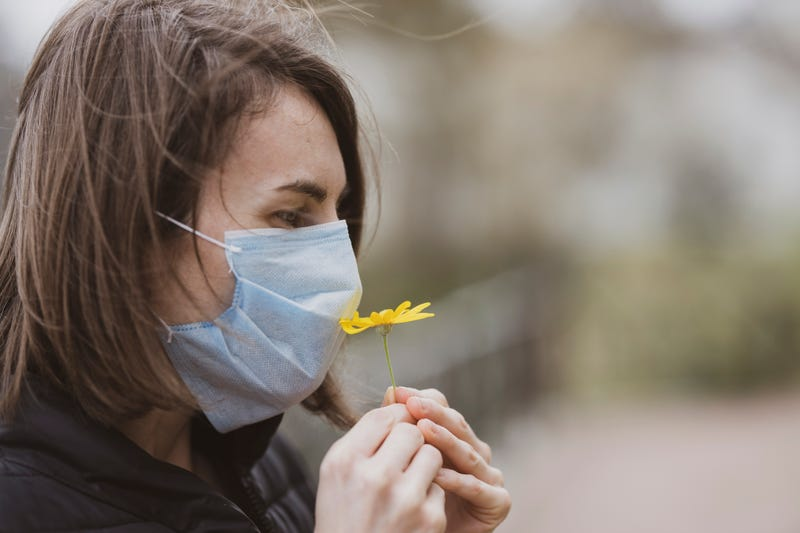 woman smelling flower through face mask