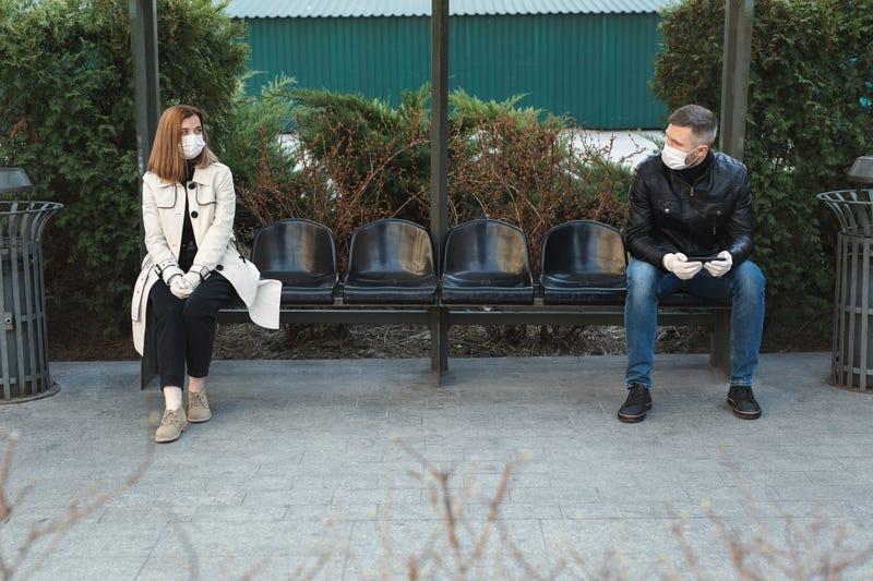 personas en mascarilla sentadas en una banca