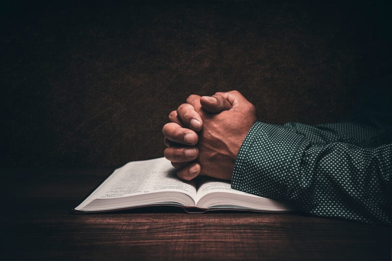 The hands of a church pastor praying over an open bible in his desk.
