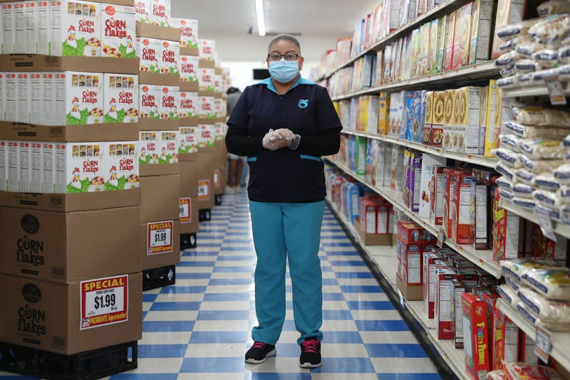 Lorena Martinez poses for a picture as she wears a mask and gloves while working at the Presidente Supermarket on April 13, 2020 in Miami, Florida. The employees at Presidente Supermarket, like the rest of America's grocery store workers, are on the front lines of the coronavirus pandemic, helping to keep the nation's residents fed.