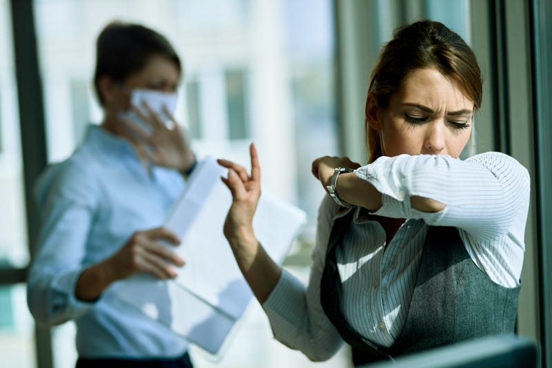 woman coughing into elbow with woman behind her in face mask