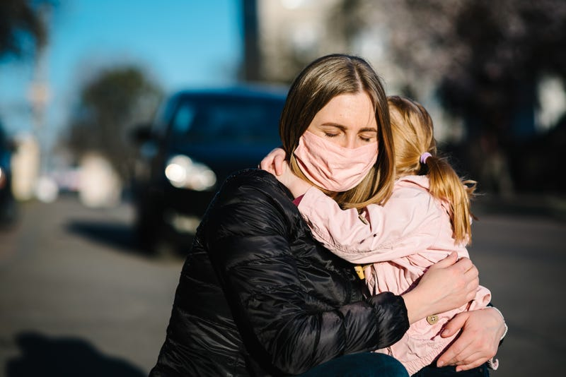 woman in facemask hugs child