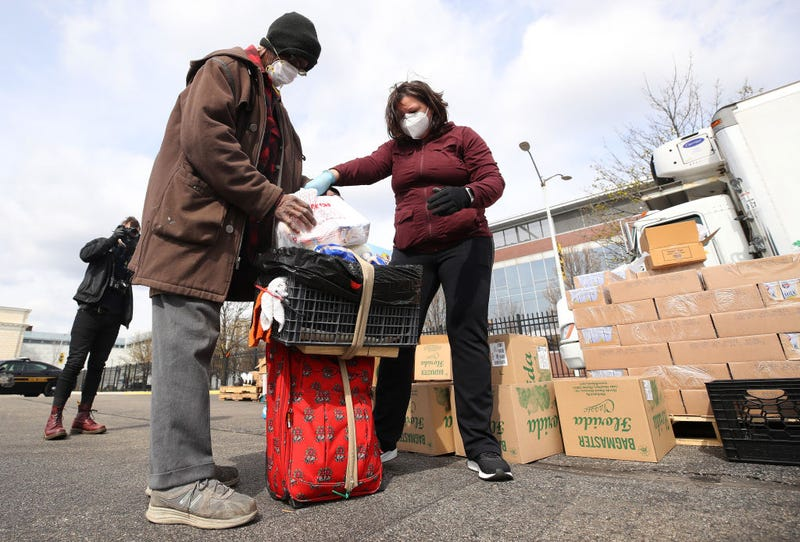 A volunteer with Forgotten Harvest loads food into a cart at a mobile pantry April 14, 2020 in Detroit, Michigan. The organization distributes food throughout the metro area, which has seen an uptick in demand due to the COVID-19 pandemic.