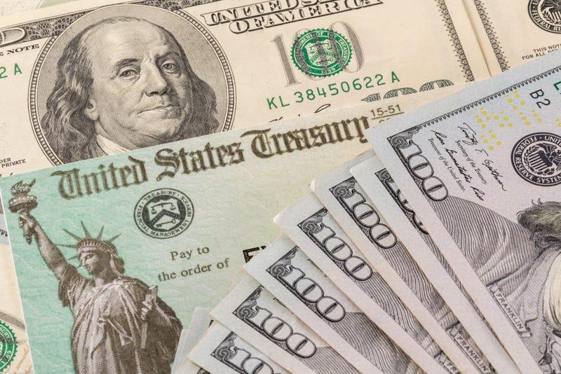 Stack of 100 dollar bills with illustrative coronavirus stimulus payment check