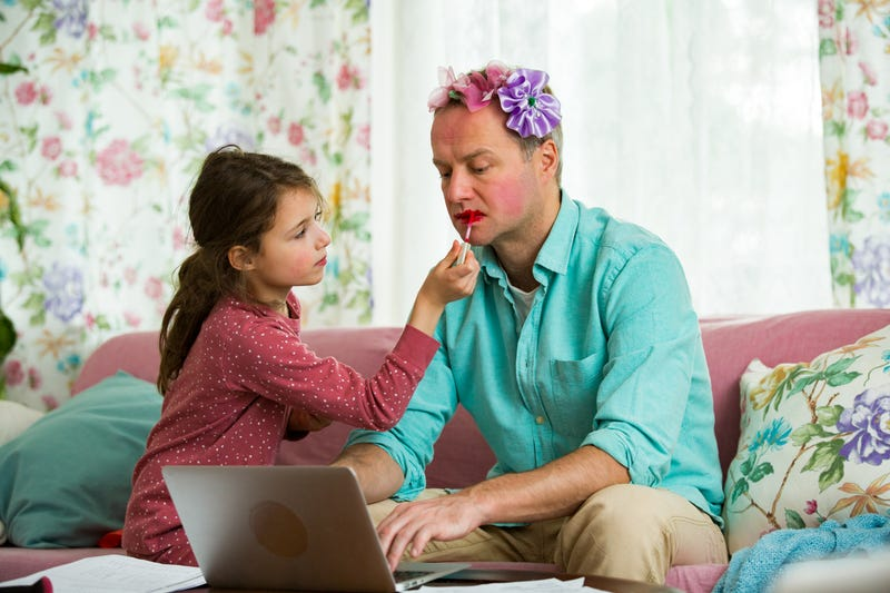 Child playing and disturbing father working remotely from home. Little girl applying makeup. Man sitting on couch with laptop.