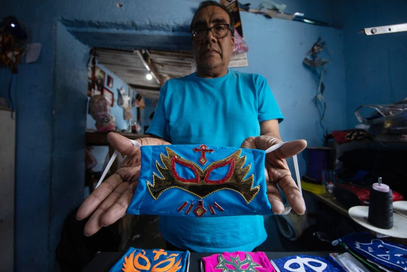 Former Mexican Lucha Libre wrestler, Isaac Huerta 'El Gato Gris', shows a 'Caristico' wrestler face mask on April 20, 2020 in Puebla, Mexico. Due to the COVID-19 pandemic, Huerta turned to produce themed protective masks in his own Lucha Libre masks studio, using the same materials.
