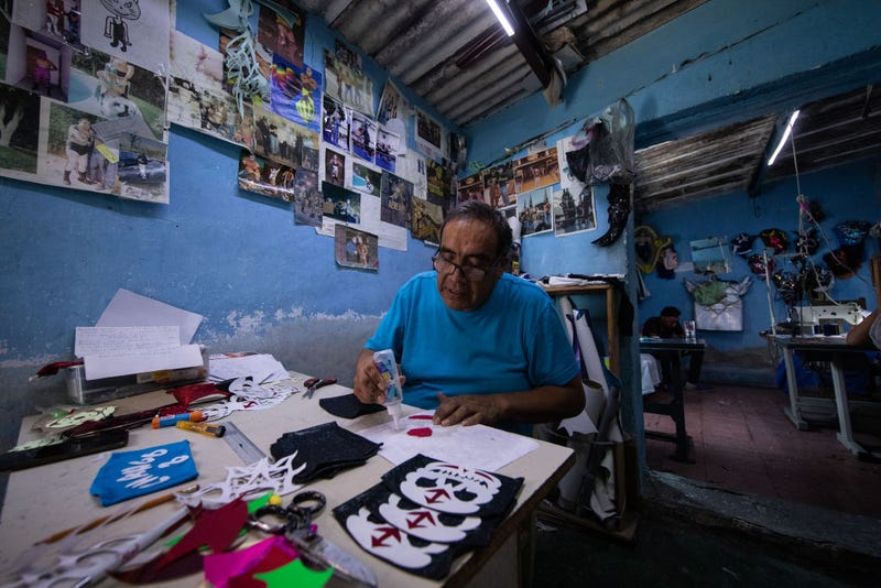 Former Mexican Lucha Libre wrestler, Isaac Huerta 'El Gato Gris', makes face masks of Mexican Lucha Libre wrestlers on April 20, 2020 in Puebla, Mexico. Due to the COVID-19 pandemic, Huerta turned to produce themed protective masks in his own Lucha Libre masks studio, using the same materials.