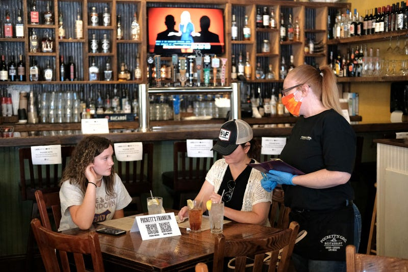 A waitress wearing rubber gloves and a mask is seen taking orders for patrons at Puckett's Grocery & Restaurant on April 27, 2020 in Franklin, Tennessee. Tennessee is one of the first states to reopen restaurants after the onset of the coronavirus (COVID-19). Restaurants are allowed to open at 50% capacity and maintain social distancing.