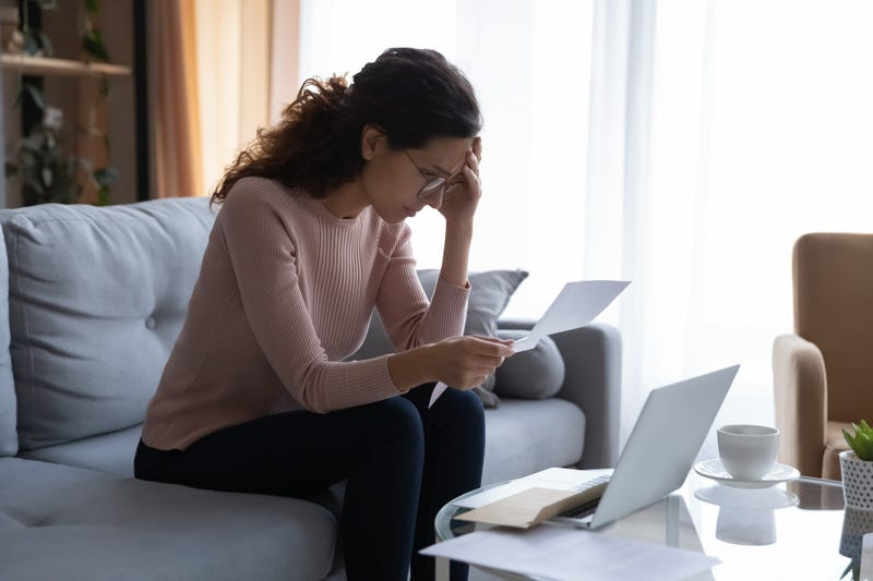 upset woman looks at piece of paper