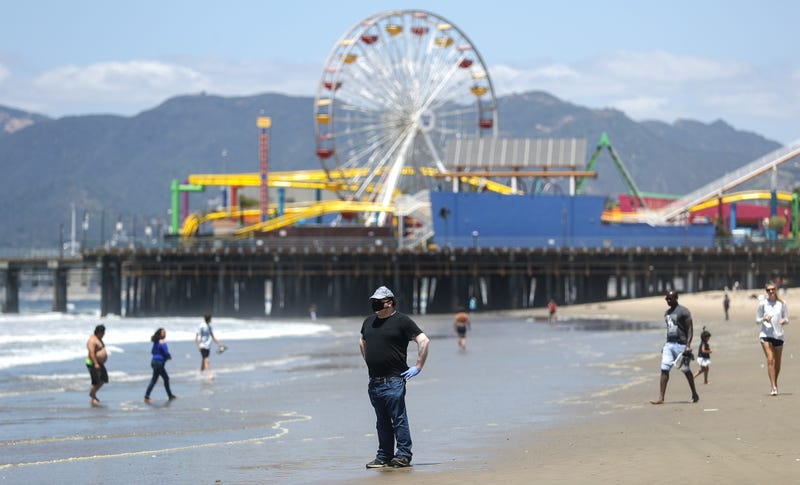 A man wears a face mask and gloves on Santa Monica beach on the day Los Angeles County reopened its beaches, which had been closed due the coronavirus pandemic, on May 13, 2020 in Santa Monica, California.