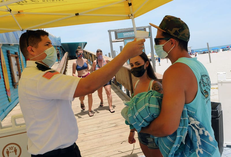 Visitors wear face masks and undergo mandatory temperature checks before entering the pier on Independence Day on July 4th in Cocoa Beach, Florida
