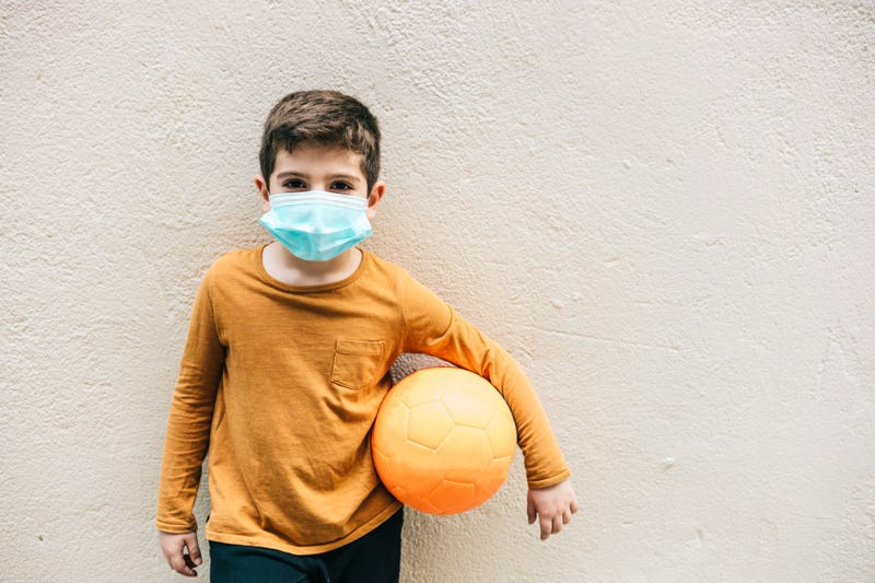 Little boy with a ball and protective mask