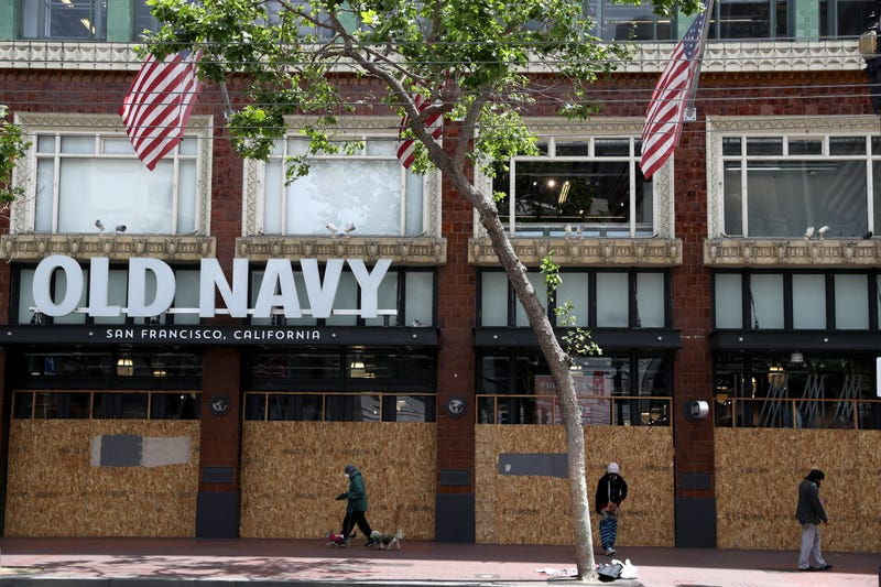 Pedestrians walk by a boarded up Old Navy store on May 15, 2020 in San Francisco, California.