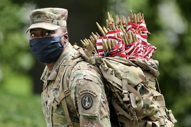 """Wearing face masks to reduce the risk of spreading the novel coronavirus, a soldier from the 3rd Infantry Regiment, or the """"Old Guard,"""" works to place U.S. flags in front of every grave site ahead of the Memorial Day weekend in Arlington National Cemetery on May 21, 2020 in Arlington, Virginia. Traditionally known as """"Flags-In,"""" soldiers place small flags in front of more than 228,000 headstones and at the bottom of about 7,000 niche rows in the cemetery's Columbarium Courts and Niche Wall . (Photo by Chip Somodevilla/Getty Images)"""