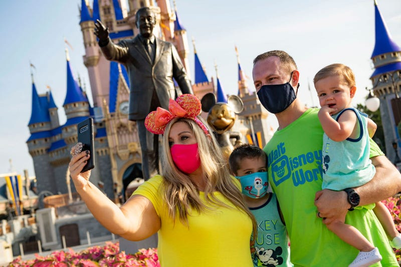 In this handout photo provided by Walt Disney World Resort, guests stop to take a selfie at Magic Kingdom Park at Walt Disney World Resort on July 11, 2020 in Lake Buena Vista, Florida. July 11, 2020 is the first day of the phased reopening.