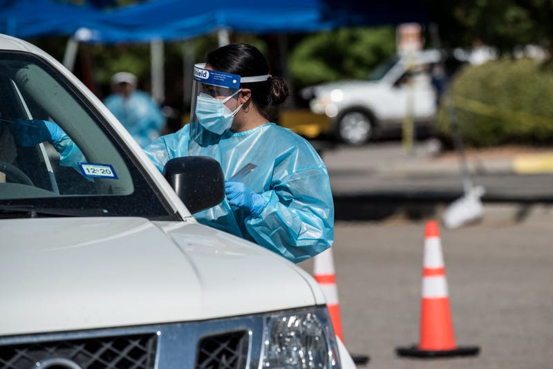 A nurse conducts a coronavirus test at a newly opened mega drive-thru site at El Paso Community College Valle Verde campus on July 21, 2020 in El Paso, Texas. As coronavirus deaths surge past 4000 in Texas, overwhelmed hospitals are being forced to plan for extra refrigerated storage to hold deceased patients.