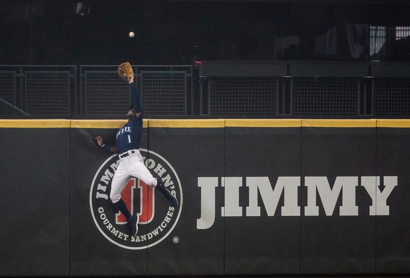 Kyle Lewis scales the center-field wall for a leaping catch