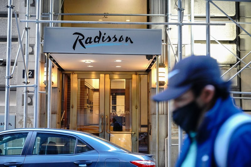 A person wearing a face mask walks past a former Radisson Hotel at Wall street that were converted to homeless shelter.