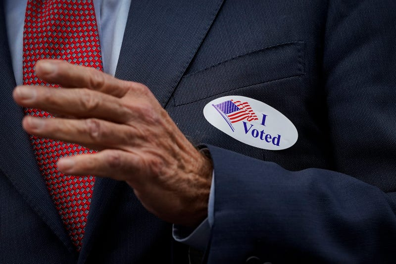 "Democratic presidential nominee Joe Biden wears an ""I Voted"" sticker as he speaks to reporters outside the Delaware State Building after casting his ballot for the general election on October 28, 2020 in Wilmington, Delaware."