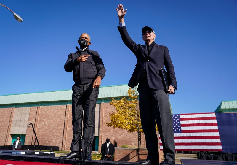 Former U.S. President Barack Obama and Democratic presidential nominee Joe Biden wave to the crowd at the end of a drive-in campaign rally at Northwestern High School on October 31, 2020 in Flint, Michigan.