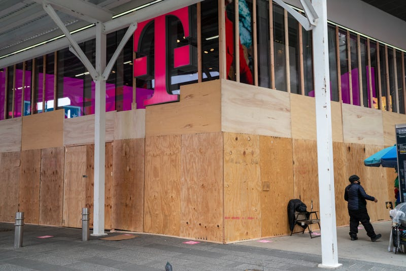A person walks by a boarded up a T-Mobile store in Times Square on November 1, 2020 in New York City.