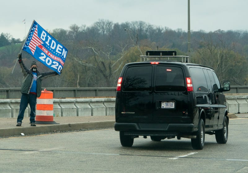 A protester holds up a sign in support of US President-elect Joe Biden, as the motorcade with US President Donald Trump passes in Washington, DC on November 26, 2020.