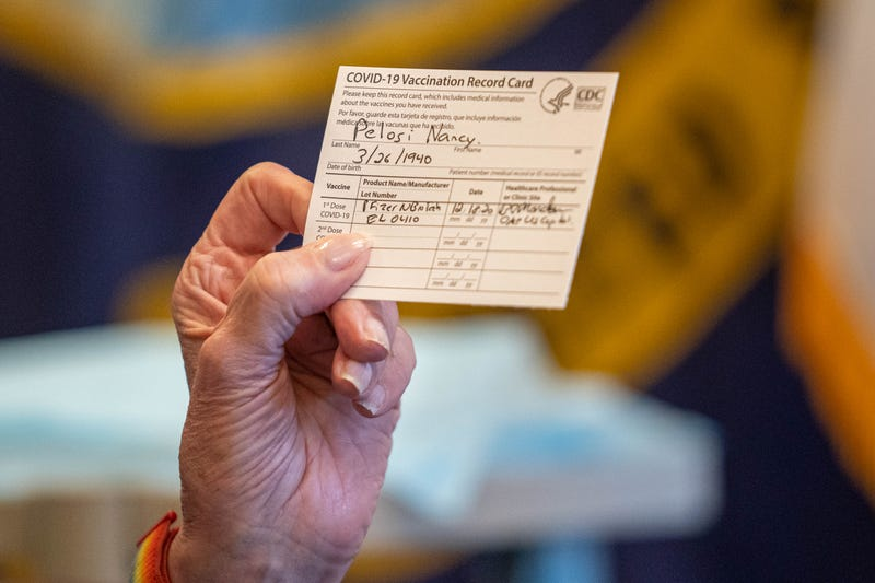 Speaker of the House Nancy Pelosi (D-CA) holds up a Vaccination Record Card after receiving a COVID-19 vaccination shot by Dr. Brian Monahan, attending physician of the Congress of the United States, in her office on Capitol Hill on December 18, 2020 in Washington, DC.