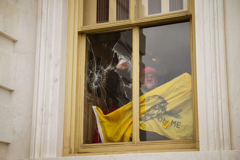 A rioter gestures from inside a broken Capitol window during insurrection by Trump supporters, Jan. 7, 2021.
