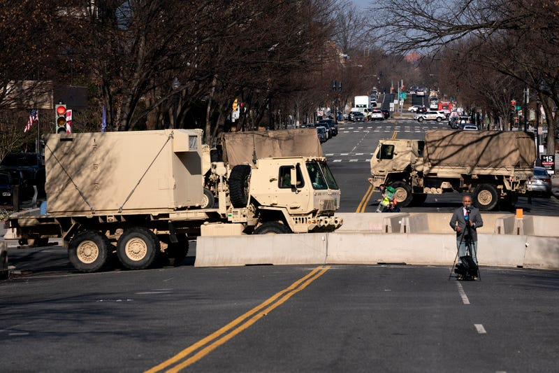 A reporter does a television hit in front of military vehicles near the U.S. Capitol on January 14, 2021 in Washington, DC. Security has been increased throughout Washington following the breach of the U.S. Capitol last Wednesday, and leading up to the Presidential Inauguration.