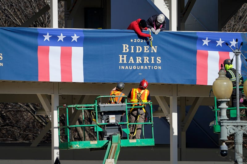 "Workers put up ""Biden-Harris"" branded bunting on a press riser along the inaugural parade route near the White House on January 14, 2021 in Washington, DC. Thousands of National Guard troops have been activated to protect the nation's capital against threats surrounding President-elect Joe Biden's inauguration and to prevent a repeat of last weeks deadly insurrection at the U.S. Capitol."