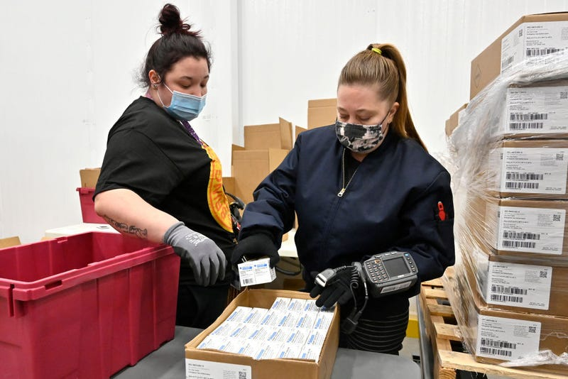 An employee with the McKesson Corporation scans a box of the Johnson and Johnson COVID vaccine as she fills an order at their shipping facility on March 1, 2021 in Shepherdsville, Kentucky. The FDA has approved a third vaccine and 3.9 million doses of J&J will begin distribution.