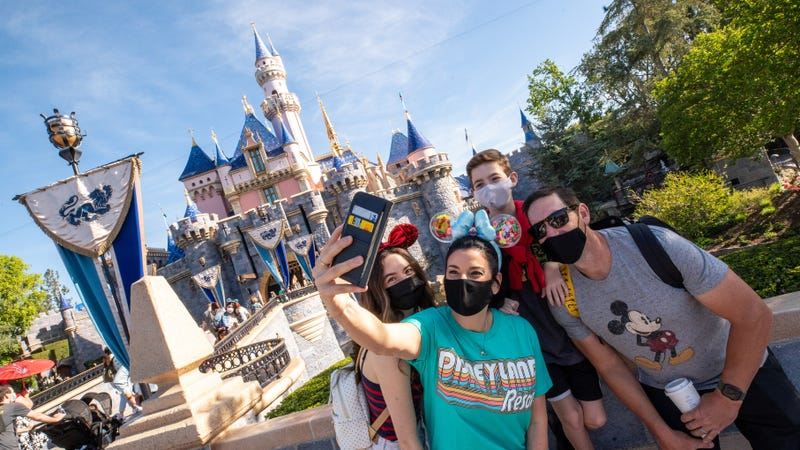 A family takes a selfie photo in front of Sleeping Beauty Castle as Disneyland Park.