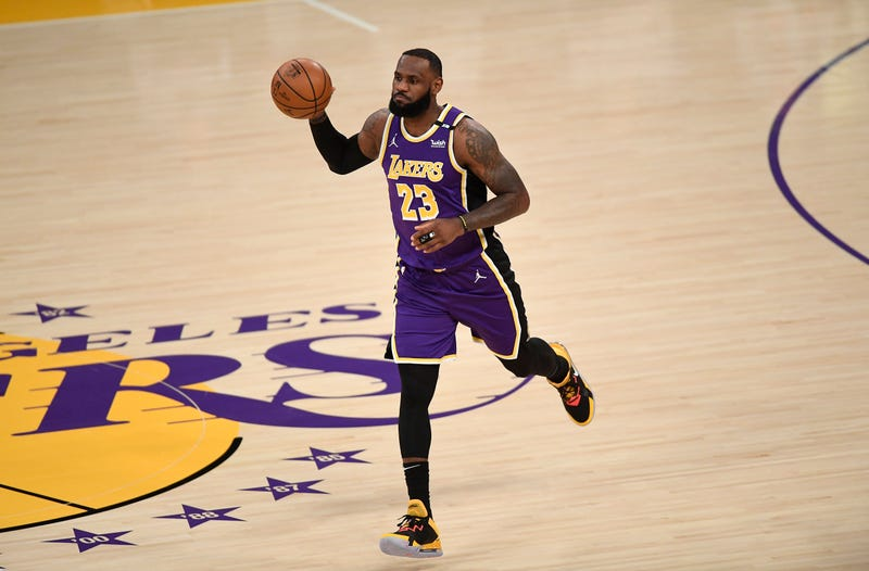 Lakers star LeBron James dribbles up the court.