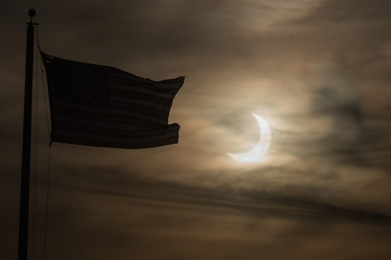 """An eclipsed sun rises next to a flag on June 10, 2021 in Scituate, Massachusetts. Northeast states in the U.S. will see a rare eclipsed sunrise, while in other parts of the Northern Hemisphere, this annular eclipse will be seen as a visible thin outer ring of the sun's disk that is not completely covered by the smaller dark disk of the moon, a so-called """"ring of fire"""""""
